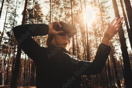 Woman in forest with virtual reality headset looking straight and trying to touch something with her hand © LALSSTOCK