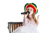 Joyful rastafarian toddler girl sinnging in a microphone and a drum