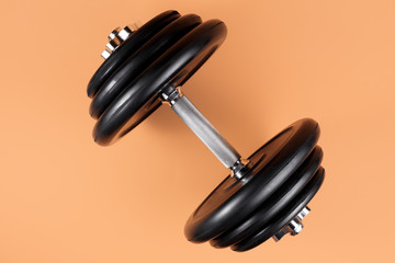 Professional dumbbell and weight plates over beige background. Black metal dumbbell with chrome silver handle. Gym equipment. Fitness concept. © Screaghin