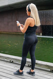 Back view of woman runner start music on smartphone before running
