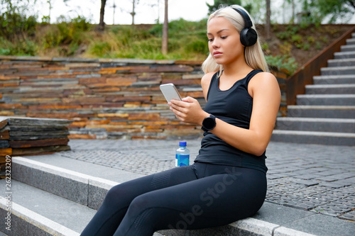 Beautiful sports woman sitting at stairs listen to music from smartphone - 262323209
