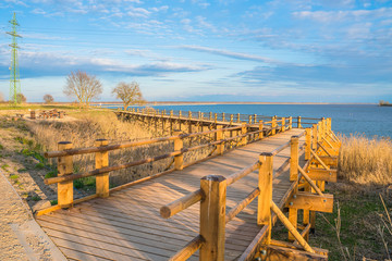 Pedestrian wooden bridge in the park. Place to rest near the lake. View of the park at sunset.