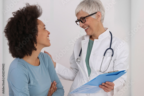 Leinwanddruck Bild Mature Doctor comforting young Woman Patient. Good news concept. Professional medical help,support, advice Female health , gynecology concept