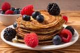Pancakes with blueberries and strawberries and cup of red juice on wooden background. Close Up. Soft focus.