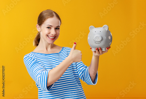 happy woman with piggy money bank on pink background. financial planning concept © JenkoAtaman