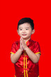 Chinese New Year Concept, Cute Asian boy in red traditional Chinese suit isolated on red with clipping path.
