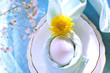 Easter table setting. Egg in a napkin decorated with a dandelion on a plate, in the form of leaves...