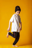 Cheerful little boy, dressed in sweatpants and a white T-shirt, actively dancing, standing on one leg. yellow background