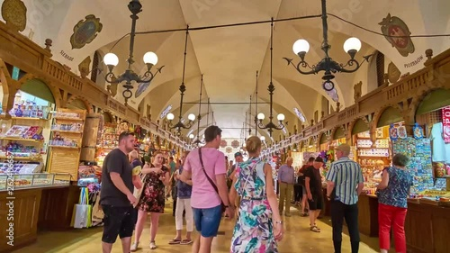 KRAKOW, POLAND - JUNE 11, 2018: Walk along the crowded medieval gallery of the Cloth Hall with many handicraft stalls and souvenir shops, on June 11 in Krakow
