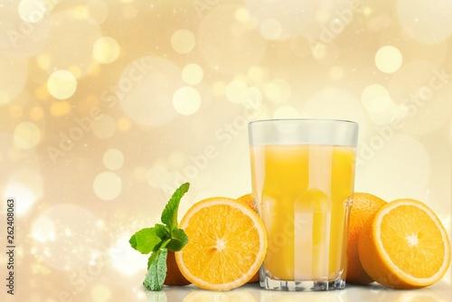 canvas print picture Orange juice and slices of orange on background