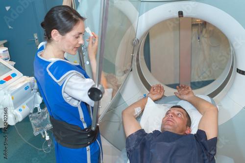 nurse guiding patient entering mri scanner © auremar