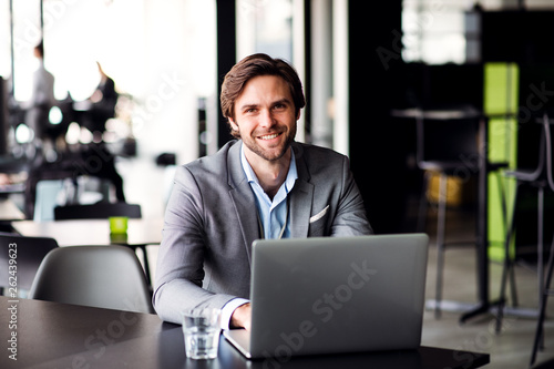 canvas print picture A portrait of young businessman with computer in an office, looking at camera.