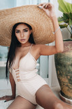 Sexy asian woman in a beige swimsuit and big hat sitting on the floor