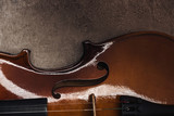 top view of classical wooden cello on grey textured surface in darkness