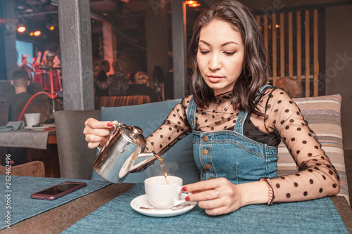 A woman pours tea from a kettle in a restaurant