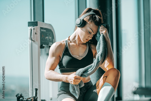 Serious muscular strong female bodybuilder with ponytail and headphones wiping sweat while sitting in gym next to window. The start is what stops most people. © dusanpetkovic1
