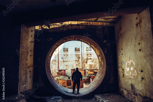 canvas print picture Man traveller inside round door or gate of abandoned nuclear rector or generator room in ruined and destroyed Nuclear Power Plant