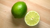 Whole lime and half rotating top view on wooden background
