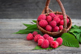 Ripe raspberries in a basket on a wooden background.