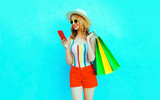Portrait happy smiling woman holding phone with shopping bags in colorful t-shirt, summer straw hat, sunglasses, red shorts on blue background