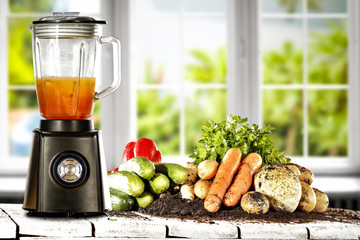 Blender in kitchen on wooden table with white window and fresh vegetables