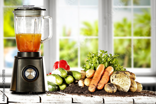 canvas print picture Blender in kitchen on wooden table with white window and fresh vegetables