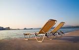 2 chairs near water. Sunset