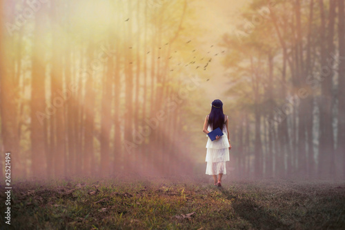 canvas print picture Woman holding a book and walking to forest.