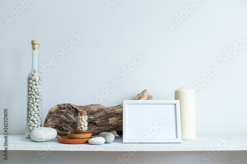 Shelf against white wall with decorative candle, glass and rocks.