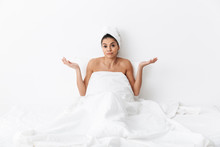 "Постер, картина, фотообои ""Beautiful confused amazing woman with towel on head lies in bed under blanket isolated over white wall background."""