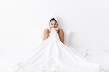 "Постер, картина, фотообои ""Scared amazing woman with towel on head lies in bed covering herself under blanket isolated over white wall background."""