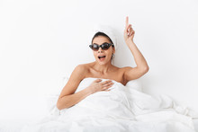 "Постер, картина, фотообои ""Excited woman with towel on head lies in bed covering body under blanket isolated over white wall background wearing sunglasses have an idea pointing."""