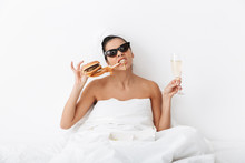 "Постер, картина, фотообои ""Emotional woman with towel on head lies in bed under blanket isolated over white wall background wearing sunglasses eat burger."""