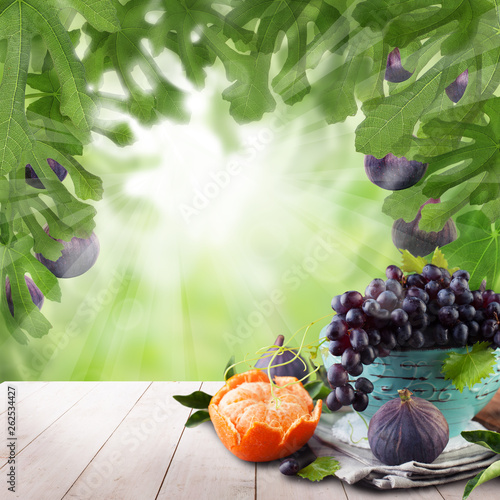 Fruit on wooden table with green tree background. Natural morning figs dessert - 262534427