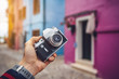 Photographer holding a retro camera in Burano