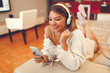 Young woman listening to music via headphones and smartphone on the sofa at home