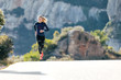 canvas print picture - Sporty young woman running on mountain road in beautiful nature.