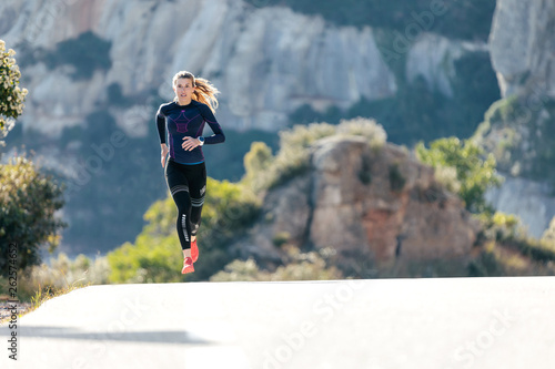 Sporty young woman running on mountain road in beautiful nature. © nenetus