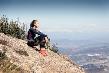 Trail runner sitting and taking a break while looking landscape from mountain peak.