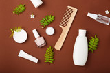 Premium skin care cosmetics, perfume on brown rustic background  with green leaves. White bottles of woman cosmetics. Natural organic cosmetics. Shampoo, tonic, cream, hairbrush, nail polish. Top view