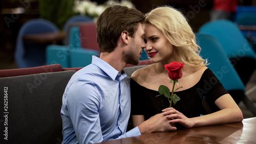 Leinwandbild Motiv Beautiful couple spending time together on date, sitting in cozy restaurant