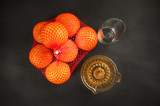 manual juicer and oranges on dark