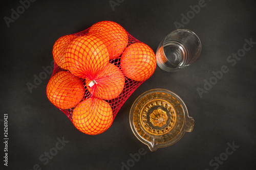 canvas print picture manual juicer and oranges on dark