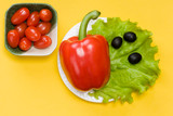 still life of bell pepper, tomato cherry, lettuce and olives on yellow background