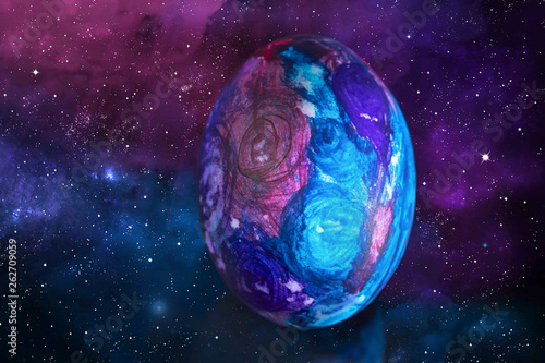 Easter egg in space style. Easter egg in space style on the background of the starry sky and the galaxy.