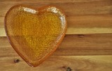 liquid flower honey in a golden heart-shaped cup on a wooden table