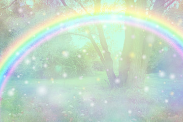 Join in the fun of an Easter egg hunt outdoors - bright arcing rainbow spanning across an orb  hazy tree landscape ideal for hiding eggs for Easter with copy space © Nikki Zalewski