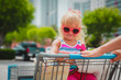 canvas print picture - shopping with kids- cute little girl in shopping cart in the city