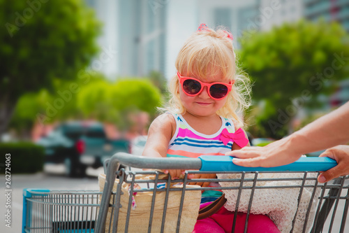 canvas print picture shopping with kids- cute little girl in shopping cart in the city