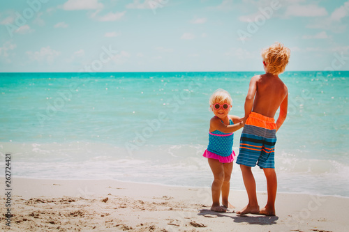 happy boy and girl play on beach vacation